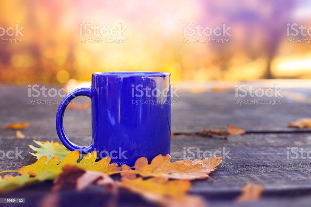 Blau Kaffeetasse auf Holztisch mit Herbst Hintergrund verwischten – Foto