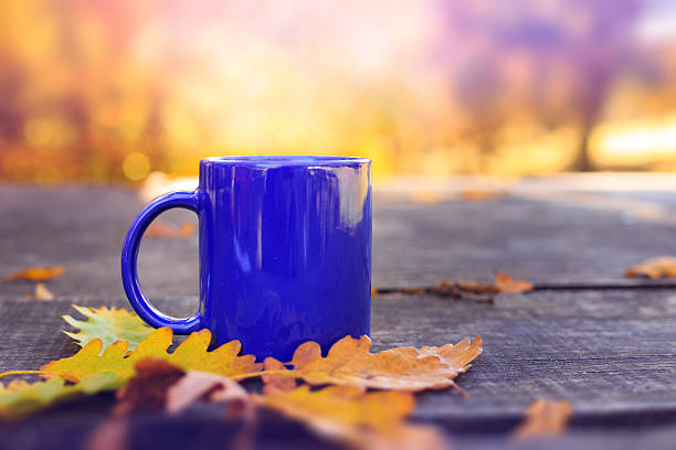 Blue cup on wooden table with autumn blurred background stock photo