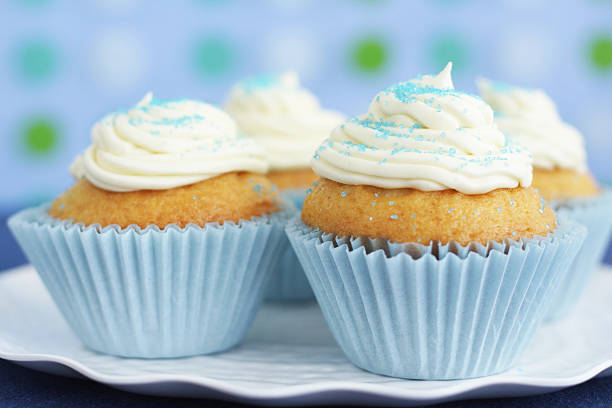 Blue cupcakes with vanilla icing on blue background Home made cupcakes on blue with vanilla icing. buttercream stock pictures, royalty-free photos & images