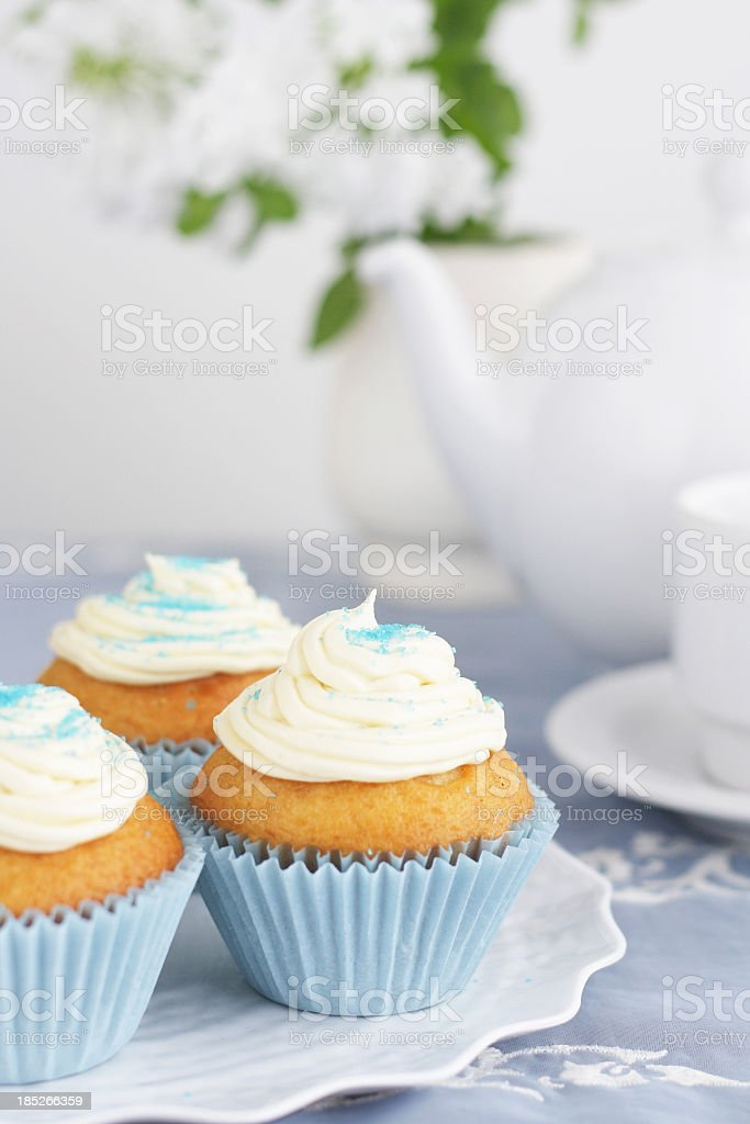 Blue cupcakes with vanilla icing with tea pot and cups background royalty-free stock photo