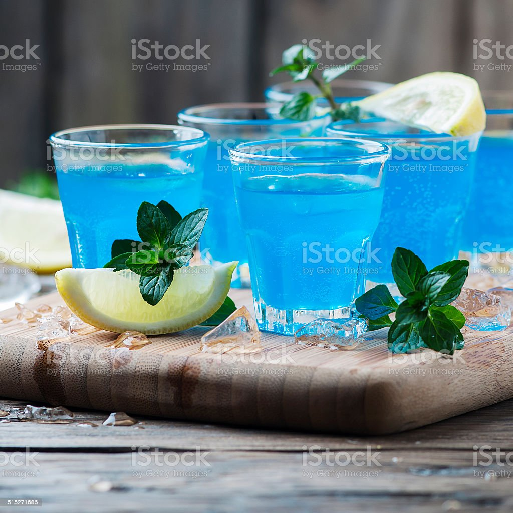 Blue curacao liqueur with lemon on the wooden table stock photo