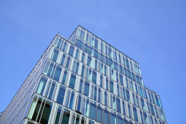 Blue curtain wall made of toned glass and steel constructions under blue sky. A fragment of a building. stock photo