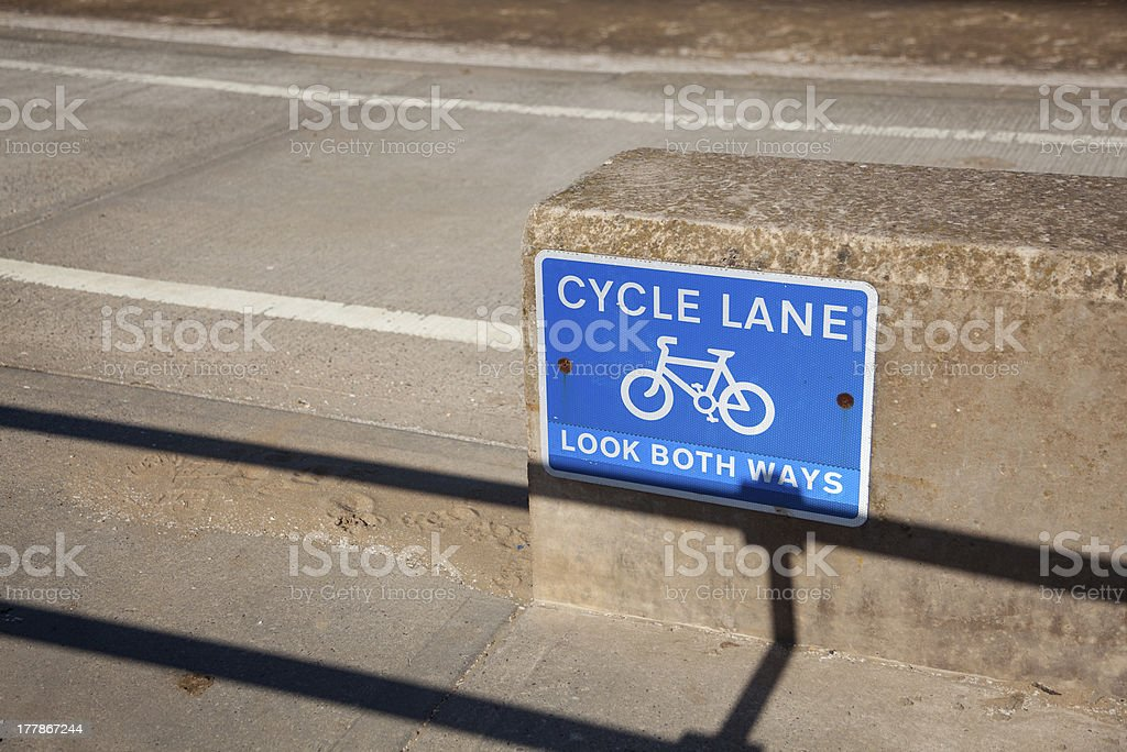 Blue cycle path lane sign by beach stock photo