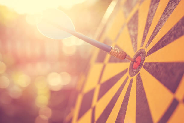blue dart arrow in the center of dartboard. blur and bokeh in sunrise time background. warm vintage effect style - sports target stock photos and pictures
