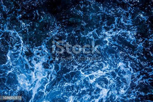 912159408 istock photo Blue deep sea foaming water background 1039532312