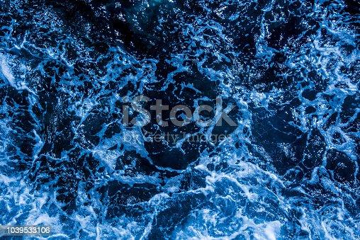 912159408 istock photo Blue deep sea foaming water background 1039533106