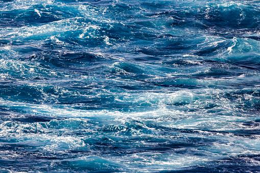 Blue deep sea foaming water background