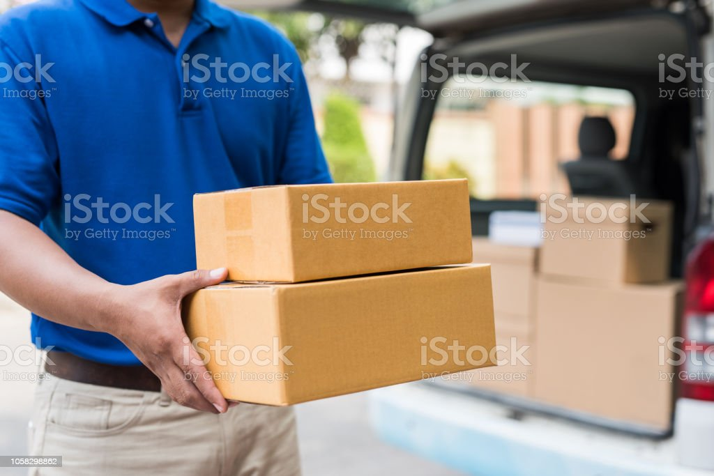 Blue delivery man holding parcel card box.