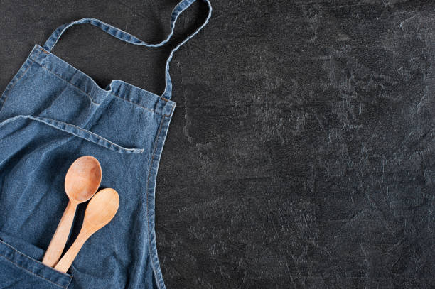 Blue denim apron with wooden spoons in the pocket Blue denim apron with wooden spoons in the pocket on the dark gray textured table, flat lay apron stock pictures, royalty-free photos & images