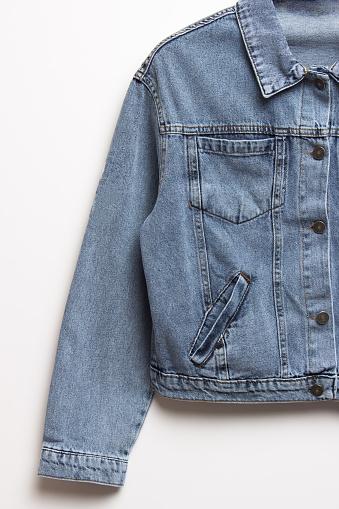 Blue denim jacket for background. Close up of the front of a denim jacket. Close-up denim jacket pocket. Denim texture background.