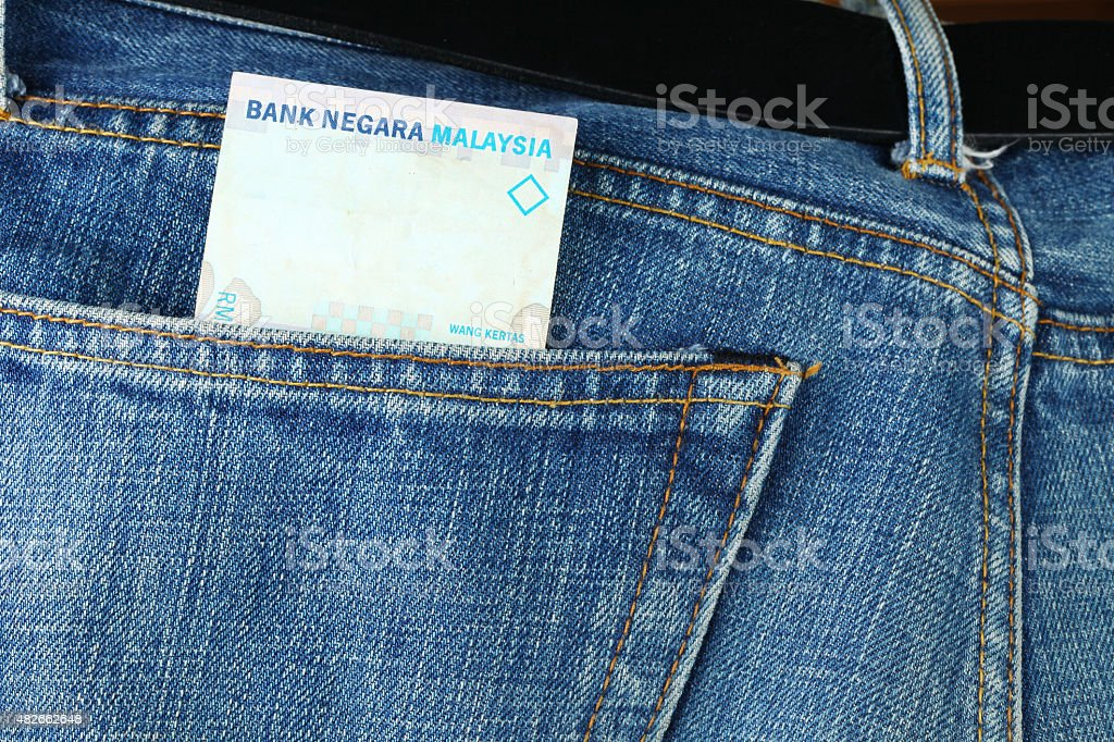 Blue denim jeans with Malaysian banknote inside. Blue denim jeans in dark color in the scene present the old denim look at the back pocket part with Malaysian banknote inside. 2015 Stock Photo