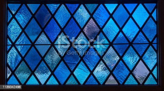 691464522 istock photo Blue diamond panes in stained glass window in american catholic church 1139342496