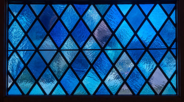 Blue diamond panes in stained glass window in american catholic church stock photo