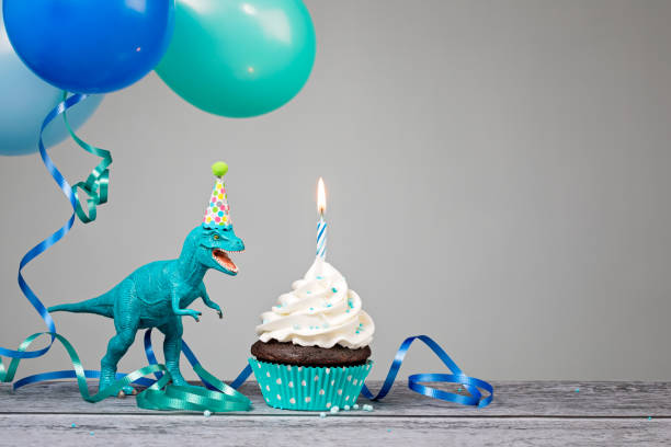 Blue Dinosaur Birthday Party Blue Dinosaur toy with birthday cupcake and balloons on a gray background. male likeness stock pictures, royalty-free photos & images