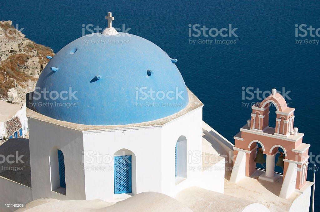 Blue dome building in Santorini Greece overlooking the ocean stock photo