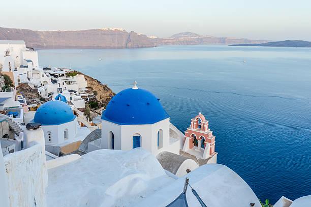 blue dome church in town of oia in santorini, greece - fira stock-fotos und bilder