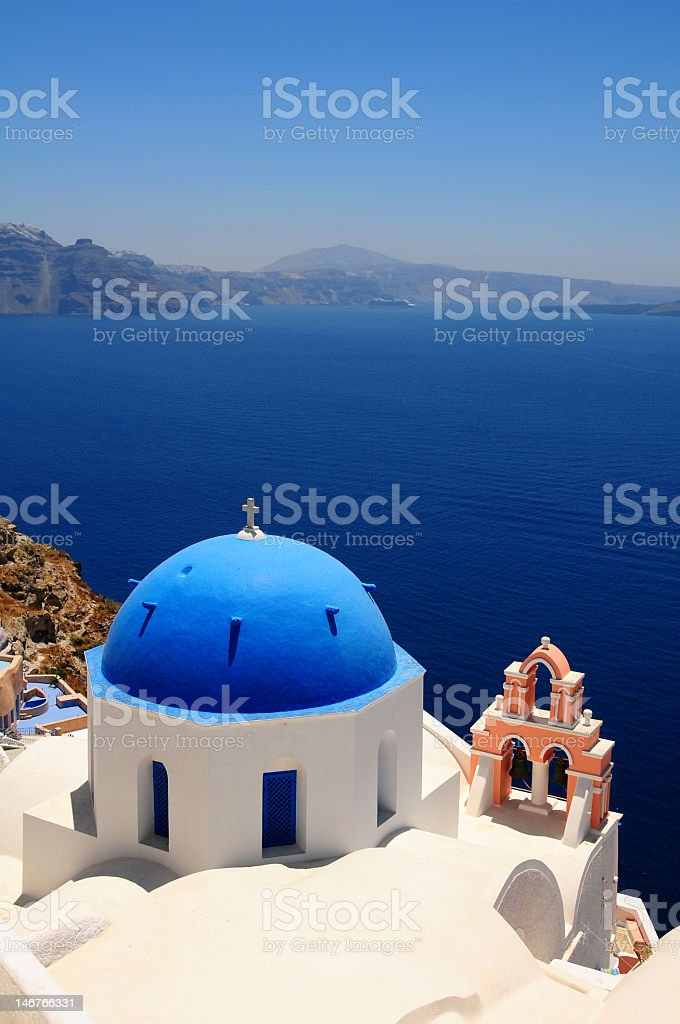 Blue done atop white building next to the sea stock photo