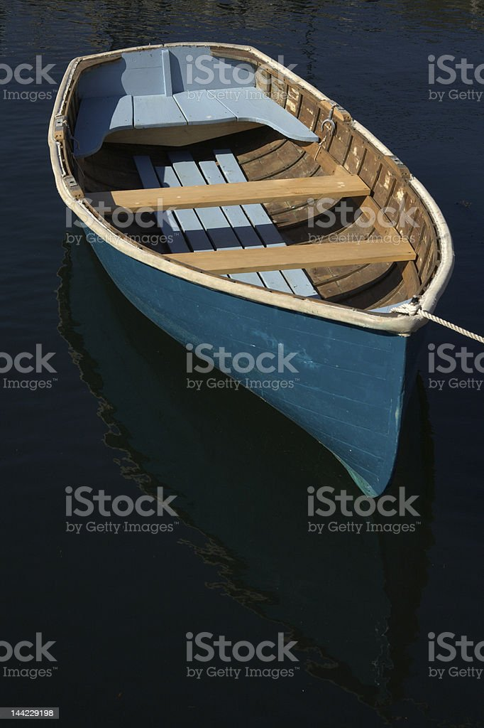 Blue dory, dinghy boat on dark water stock photo