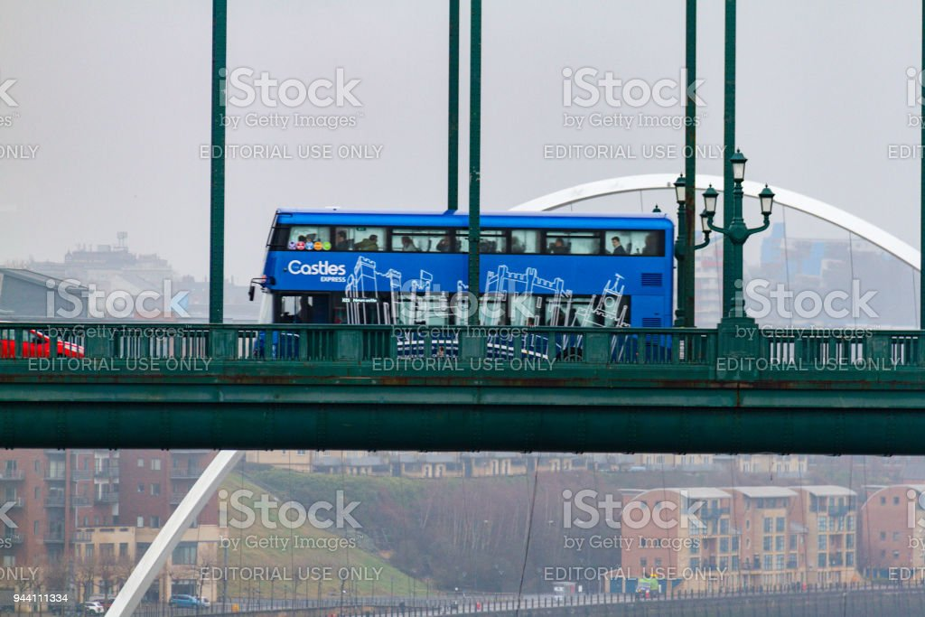 Blue double decker bus crossing the Tyne Bridge and Millennium Bridge in the distance at Newcastle Quayside on a cloudy day stock photo