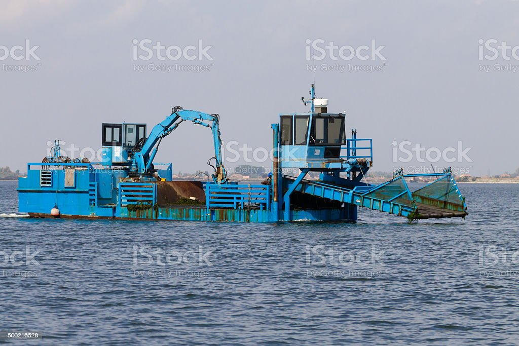 Blue dredger on water stock photo