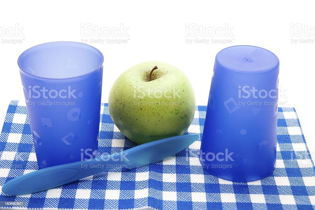 Blue drinking mugs with apple and knife royalty-free stock photo