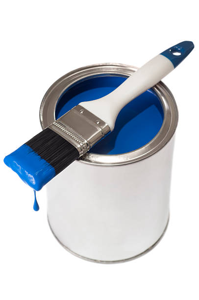 Blue dripping paint brush on a tin of paint stock photo