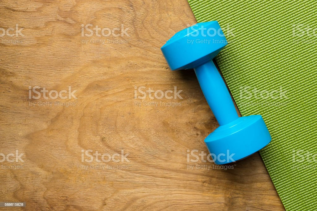 blue dumbbell on green yoga mat stock photo