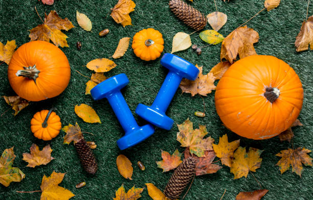 Blue dumbbells and autumn leaves with pumpkin stock photo