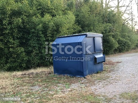 A dumpster or a skip in a field