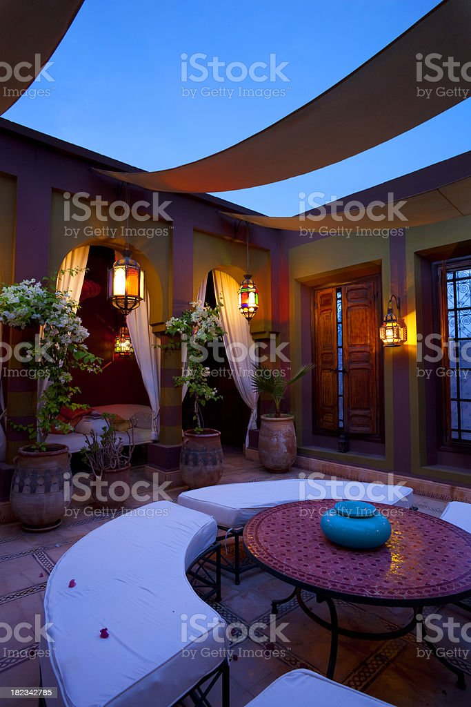 \'Dusk falls across Marrakech, bathing a luxurious courtyard in blue...
