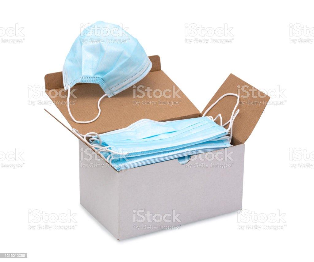 Máscaras faciales quirúrgicas de lazo de oído azul en una caja aislada sobre fondo blanco con trazado de recorte (vector). Máscara facial de procedimiento desechable con clip de nariz maleable. Máscara protectora con bandas elásticas para los oídos. - Foto de stock de Asistencia sanitaria y medicina libre de derechos