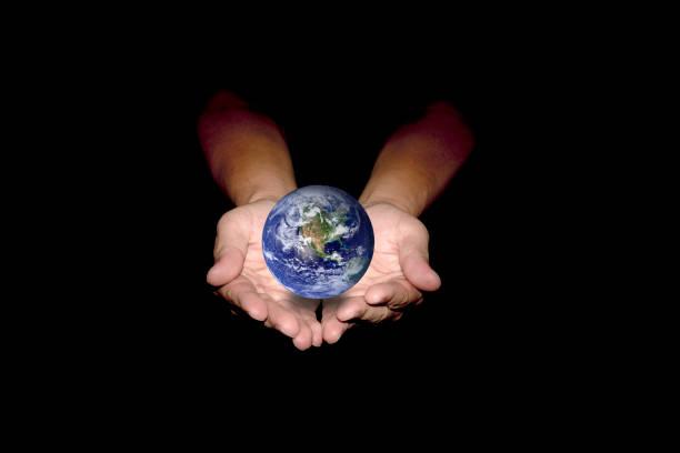 Blaue Erde in Menschenhand auf schwarzem Hintergrund isoliert. – Foto