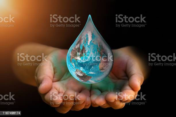 Photo of Blue Earth world with dripping water on two hand at wait on abstract black background. Water shortage and earth day concept or world water day.