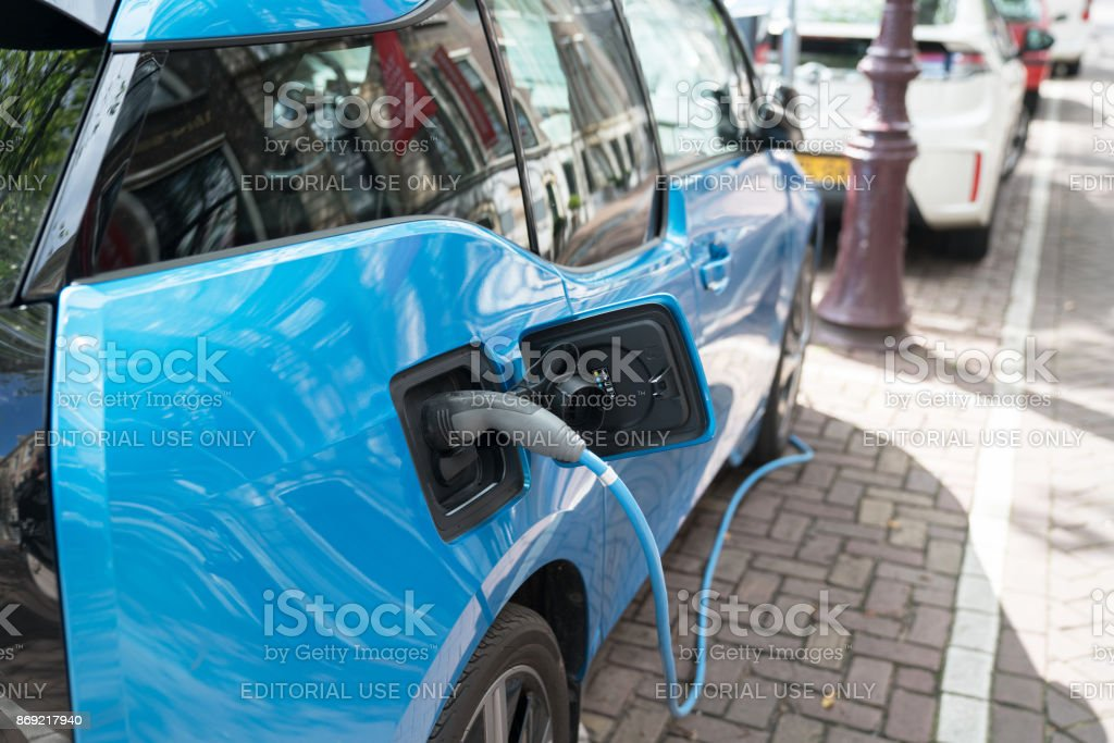 Blue electric car recharging on street with charge cable and plug...