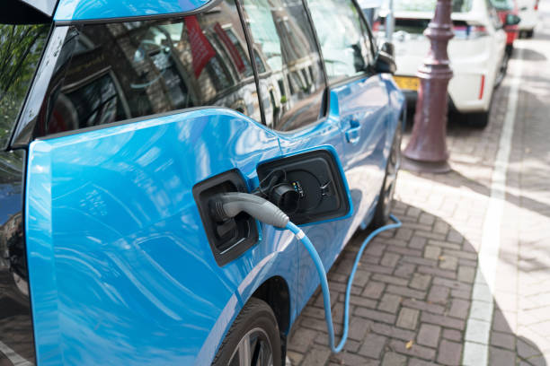 blue electric car recharging on street with charge cable and plug leading to charge point. - automobile con biodiesel foto e immagini stock