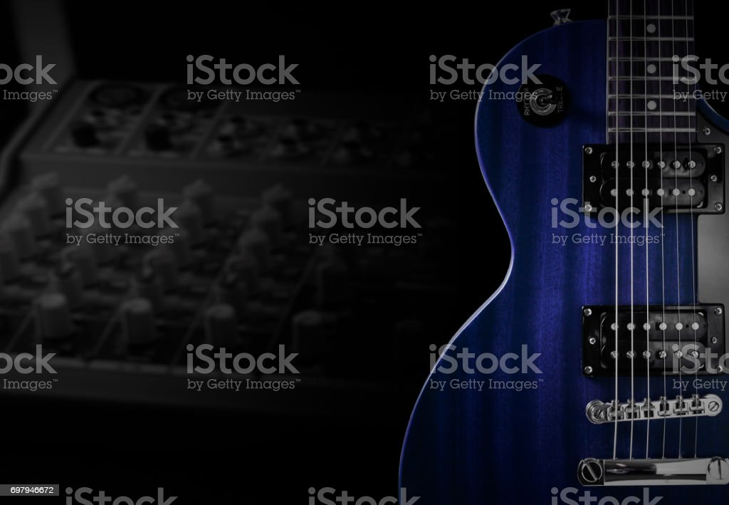 Blue electric guitar and classic amplifier on a dark background stock photo