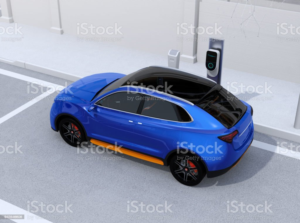 Blue electric SUV charging at parking lot with charging station in the street stock photo