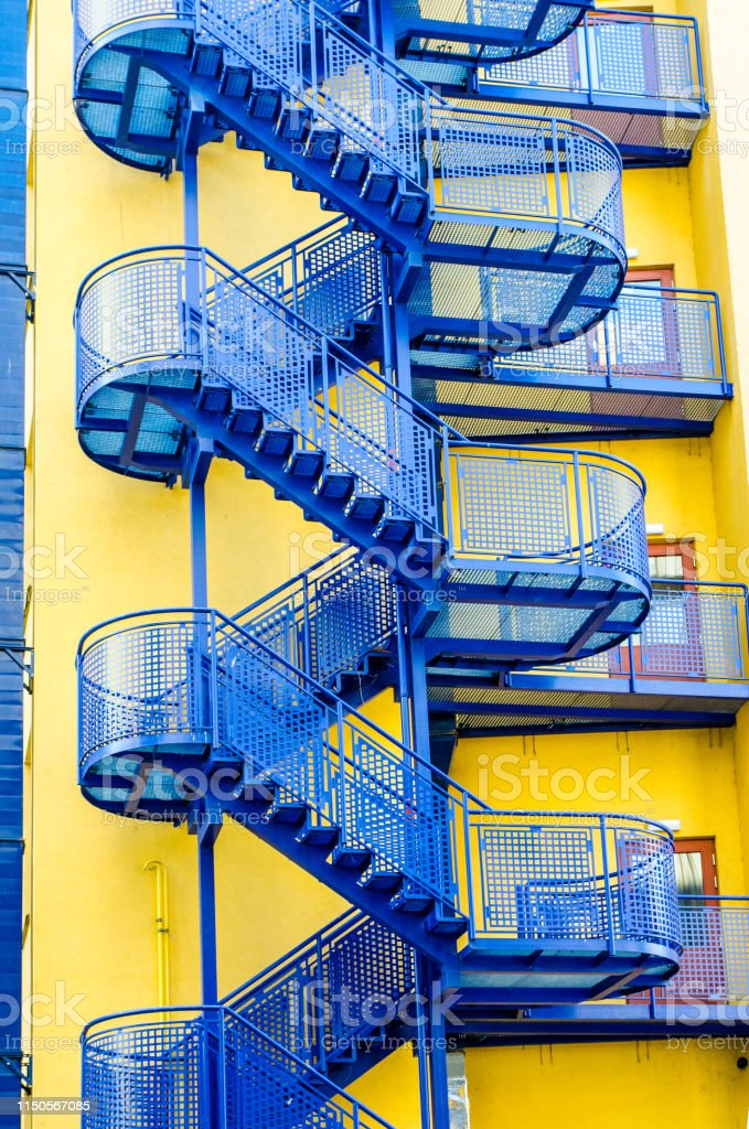 Blue emergency stairs on yellow building in Prague during day of...