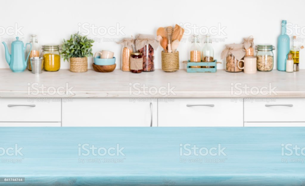 Blue empty wooden kitchen table over blurred food ingredients background stock photo