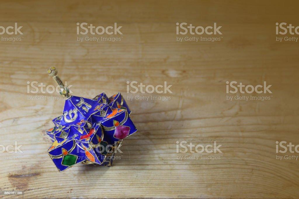 Blue enameled decorative star shaped Hanukkah dreidel on a wood table stock photo