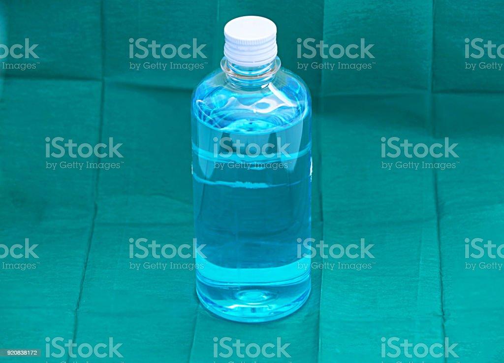 álcool etílico líquido na garrafa de plástico transparente sobre fundo verde cirurgia azul - foto de acervo