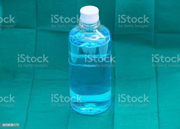 Blue Ethyl Alcohol Liquid In Plastic Transparent Bottle On Green Surgery Background Stock Photo - Download Image Now