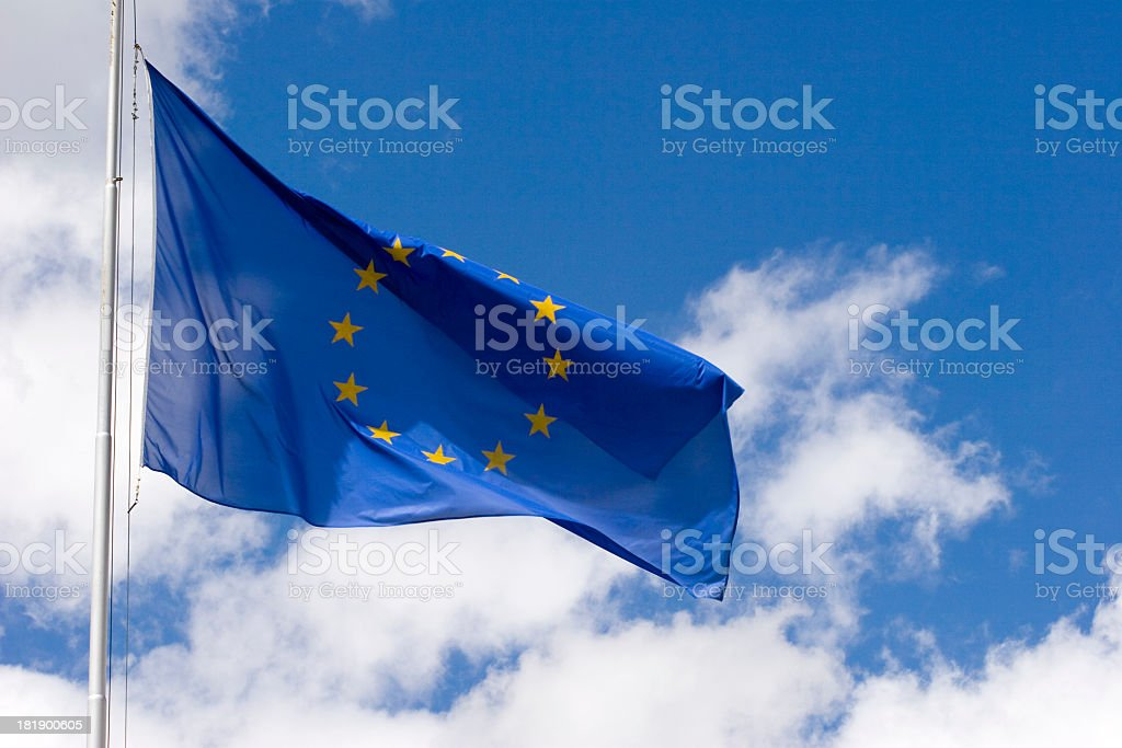 Blue EU flag on pole flying under white clouds in blue sky stock photo