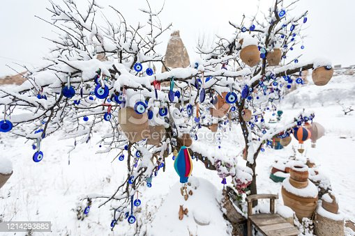 istock Blue Evil eye charms with snowy landscape in Cappadocia 1214293683