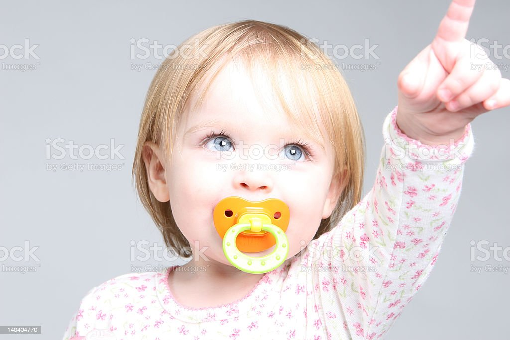 Blue eye baby girl pointing up stock photo