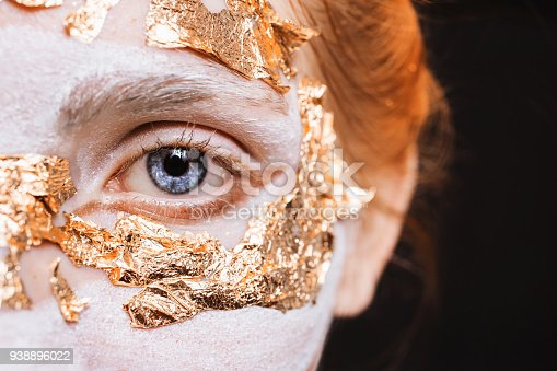 861629426 istock photo Blue eye closeup. A girl with an unusual make-up with gold leaf. Anonym. Masquerade Halloween 938896022