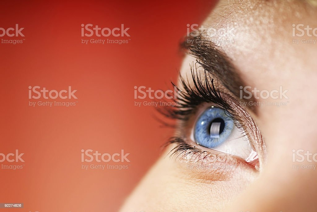 Blue eye on red background (shallow DoF) stock photo