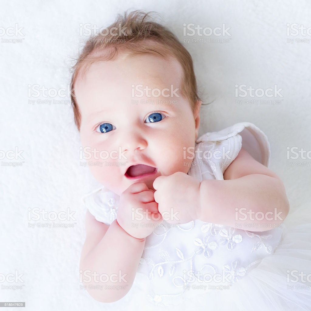 Blue eyed baby girl in a white dress stock photo