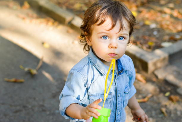 Blue eyed boy in the park with fallen leaves stock photo