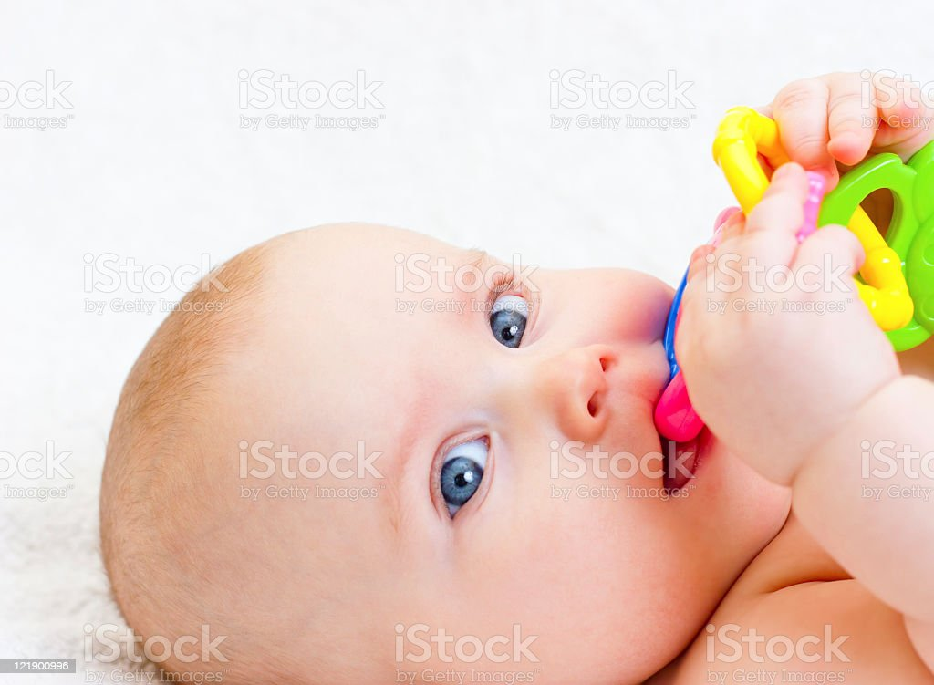 Blue eyed infant chewing on teething ring stock photo